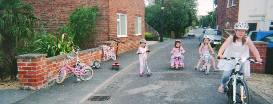 One summer in Swineshead - girls riding their bikes in the street